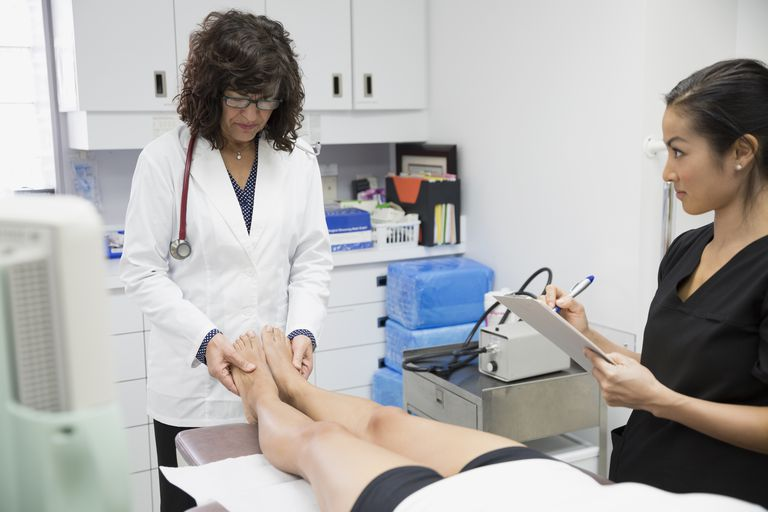 Doctor examining womans legs in examination room
