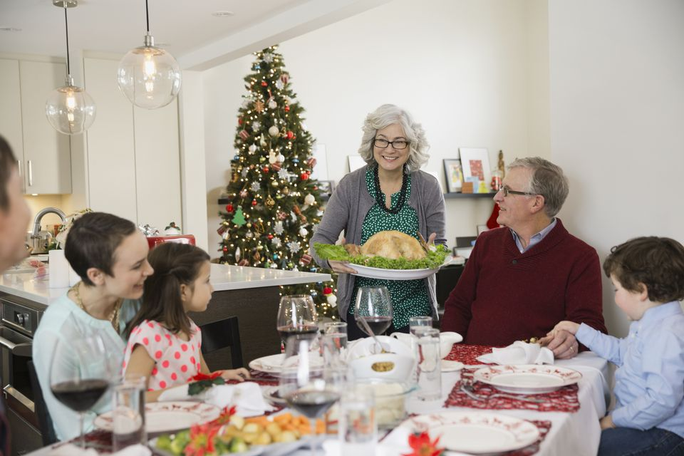 Grandmother serving turkey to family at Christmas dinner