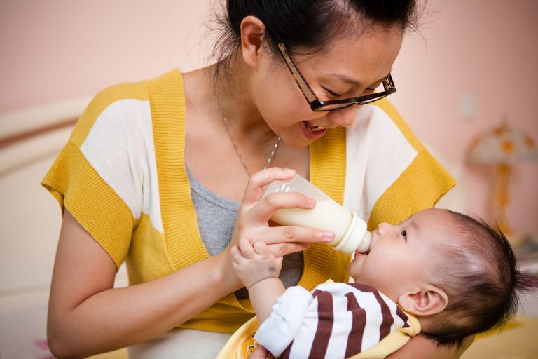 Mother feeding her baby with milk bottle