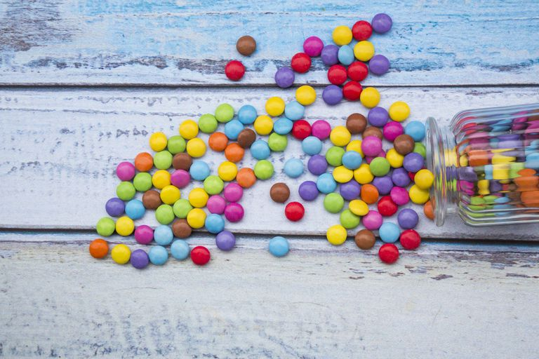 Smarties and candy jar on light blue wood