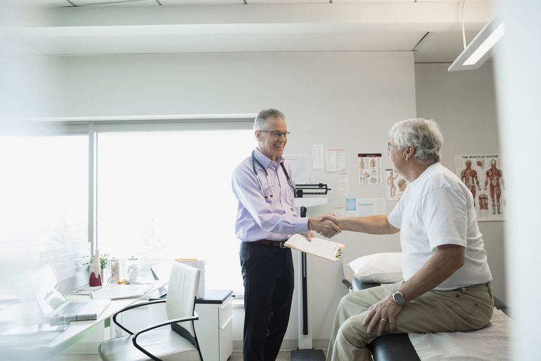 Doctor handshaking with senior man in examination room