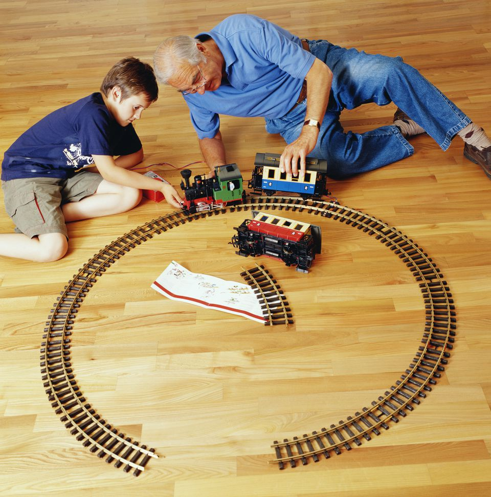 Grandson and grandfather playing with railway