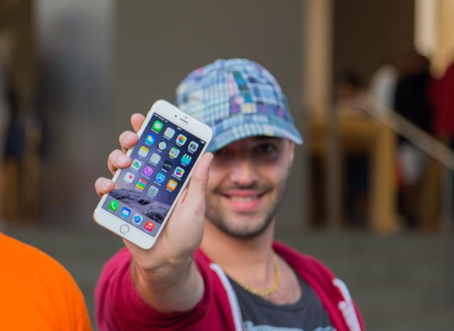 A smiling man proudly shows his newly purchased iPhone 6.