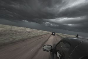 Storm clouds hovering over cars on a rural road