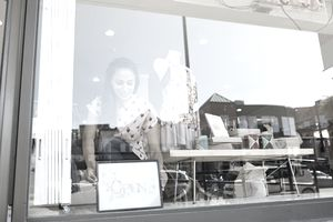 Worker placing open sign in shop window