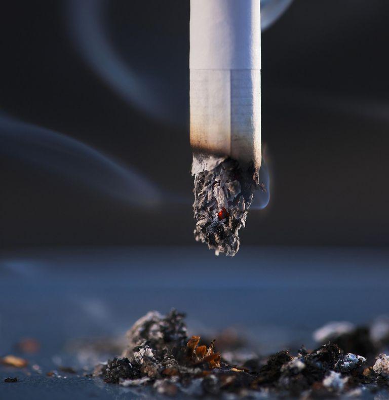 close up of lit cigarette and cigarette ash