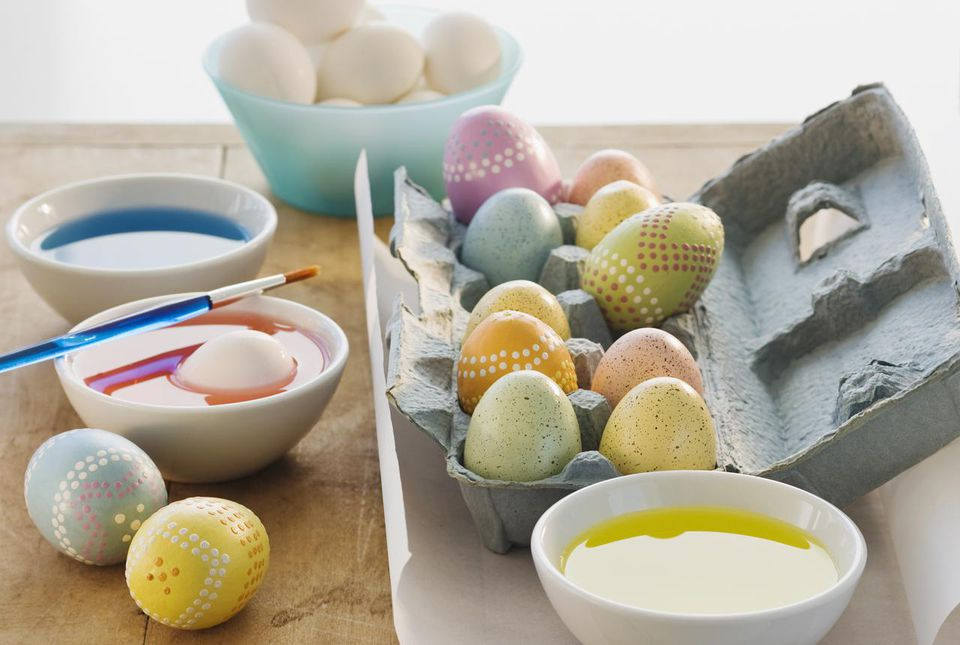Decorated eggs next to bowls of dye