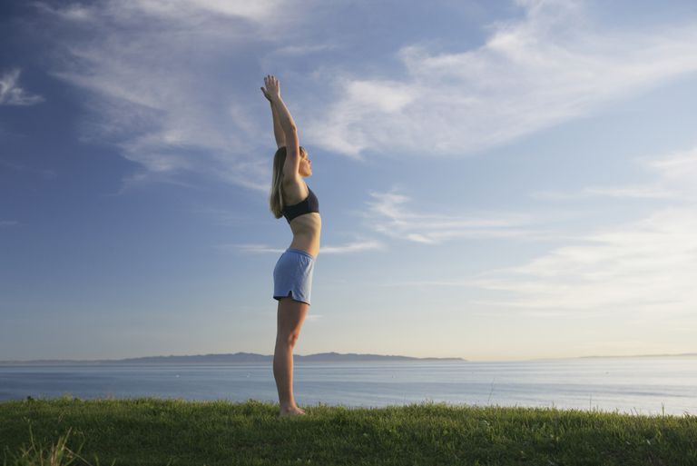Woman doing yoga on a grassy bluff