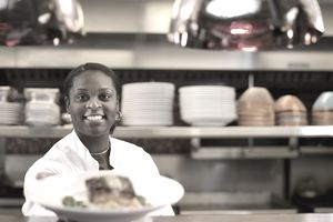 Female chef handing over a plate of food