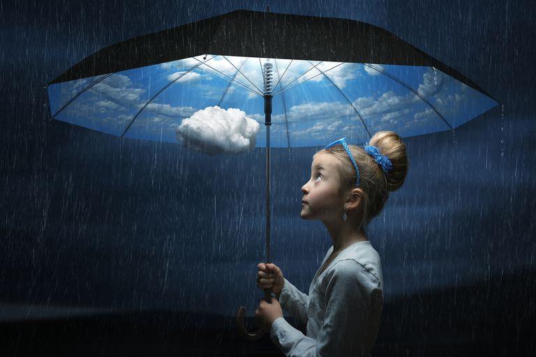 Umbrella liability insurance explained - girl standing under illuminated good weather umbrella