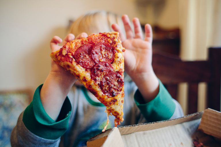 Boy holding pizza up in front of face