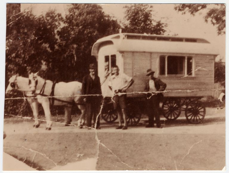 Three Gypsies pose in front of a horse-drawn caravan.