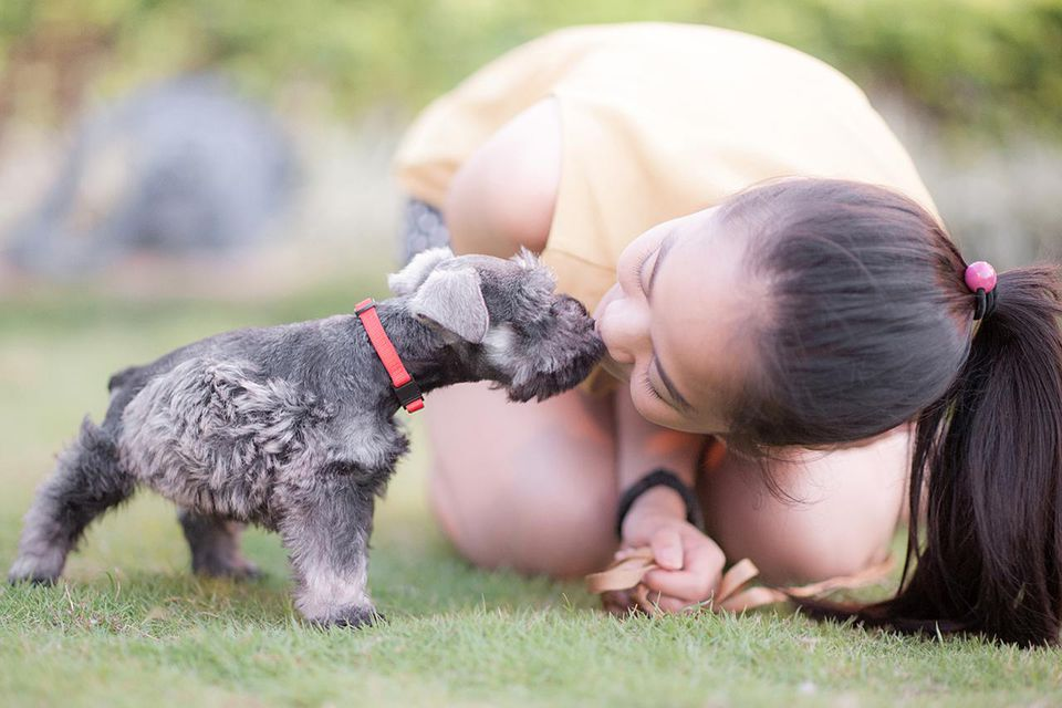 Young woman kissing her puppy.