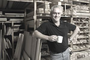 Successful man standing in his shop, happy that he hired a financial planner.