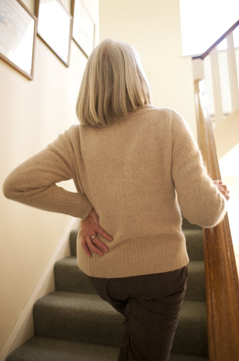 woman climbing stairs with pain