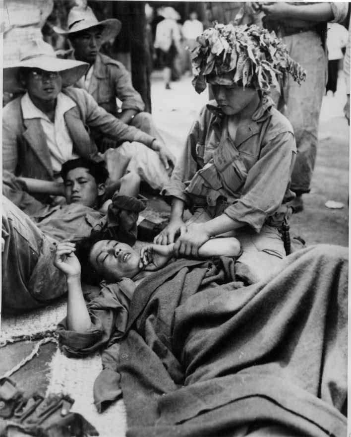Wounded Republic of Korea soldiers are tended by their fellows, July 28, 1950.
