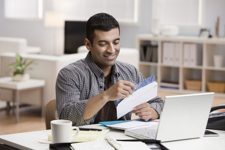 Hispanic man opening mail in home office