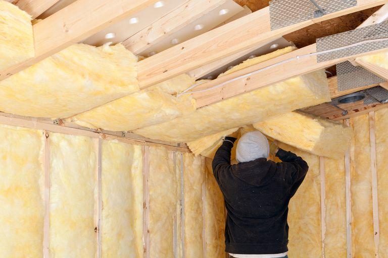 Worker Installing Fiberglass Batt Insulation between Roof Trusse