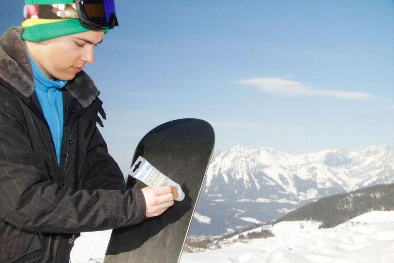 Teenage boy waxing snowboard