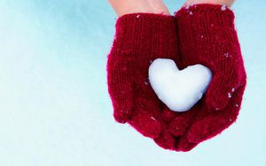 A pair of hands with red gloves holding a heart shaped snowball