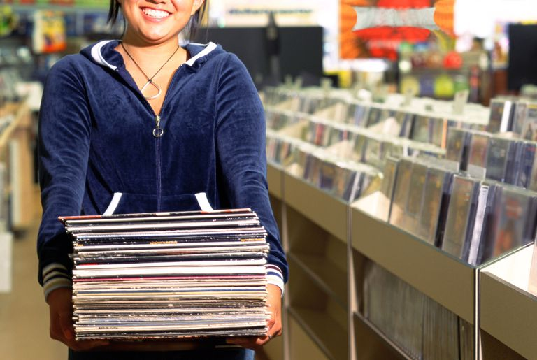 A woman holding a stack of vinyl records while standing inside a music store