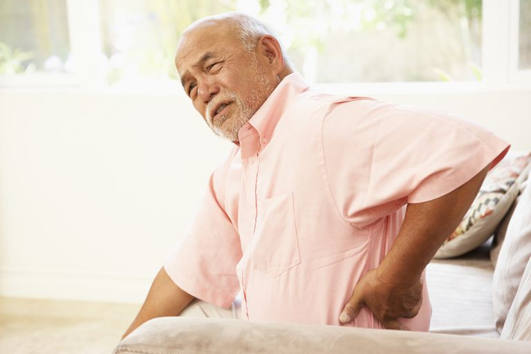 A seated man winces while touching his ribs.