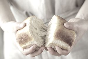 woman tearing bread apart with hands