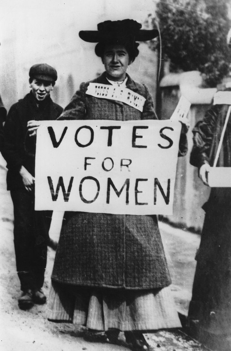 A picture of suffragist Tess Billington holding up a banner with the slogan, Votes for Women.