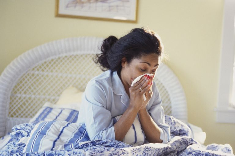 Woman with cold blowing her nose in bed