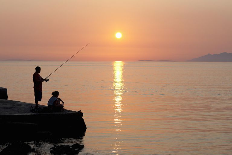Couple fishing off pier at sunset