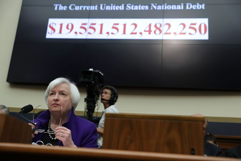 Federal Reserve Chairwoman Janet Yellen sitting in front of the national debt clock