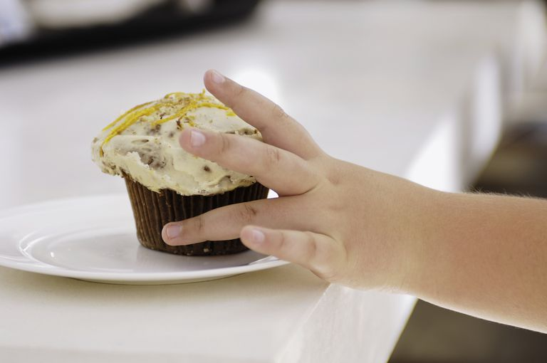 Child's hand reaching for a cupcake