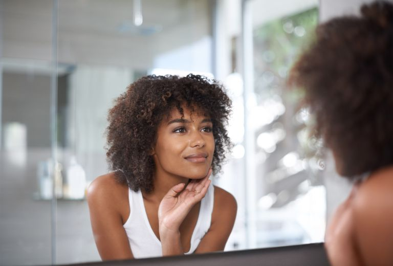 Woman with curly hair looking in mirror
