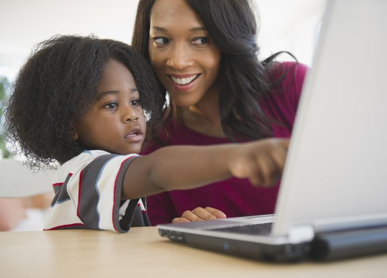 African American mother and son using lapt...