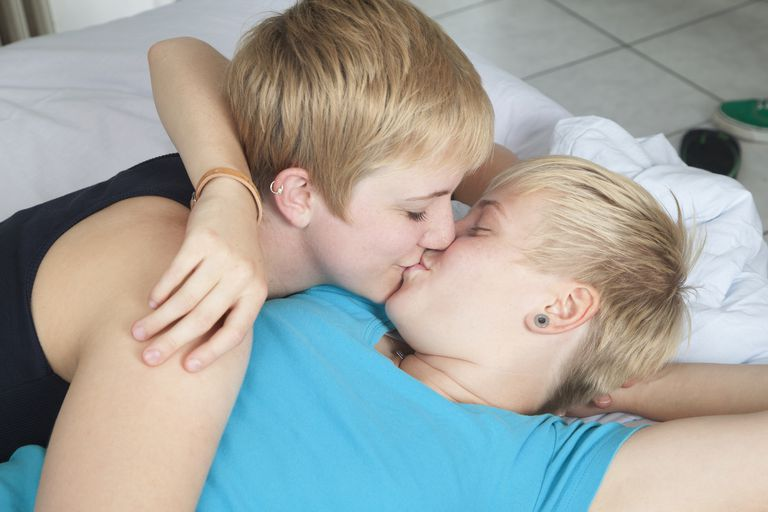 Lesbian couple kissing in bed