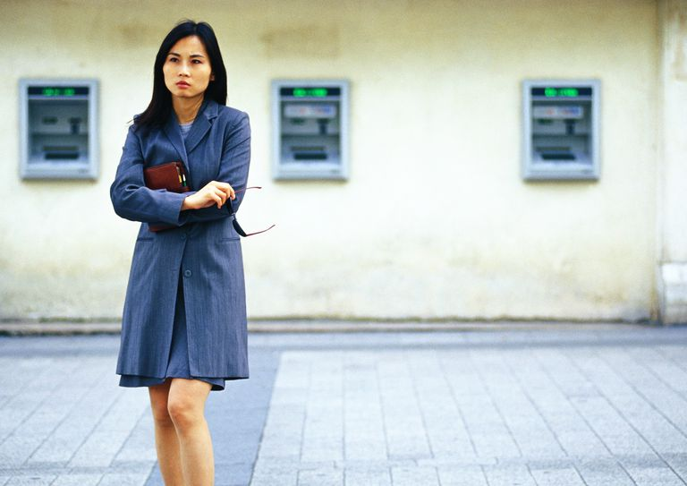 Woman in front of ATM machines, does not look happy