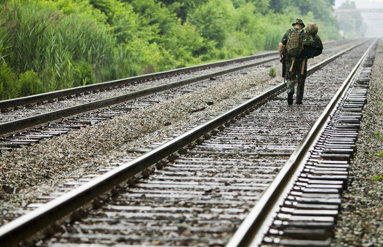 US Marine walking down train tracks, rear view