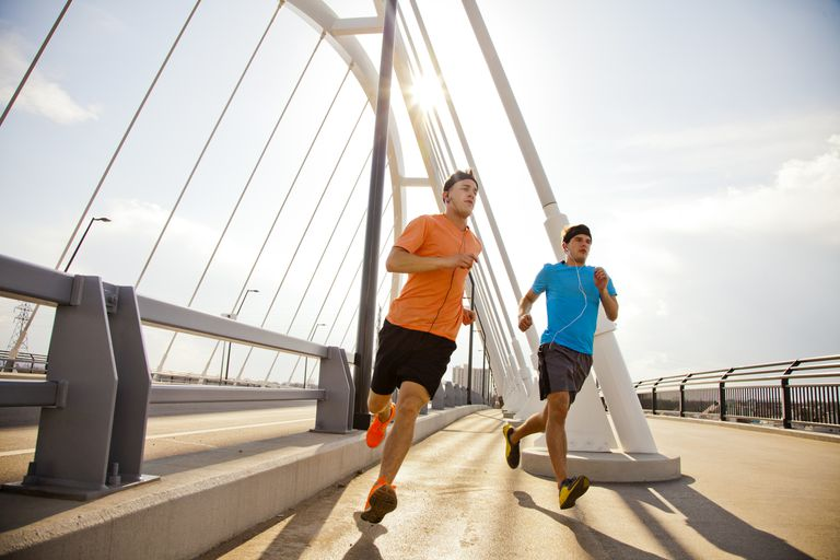Two young males jogging in an urban area together