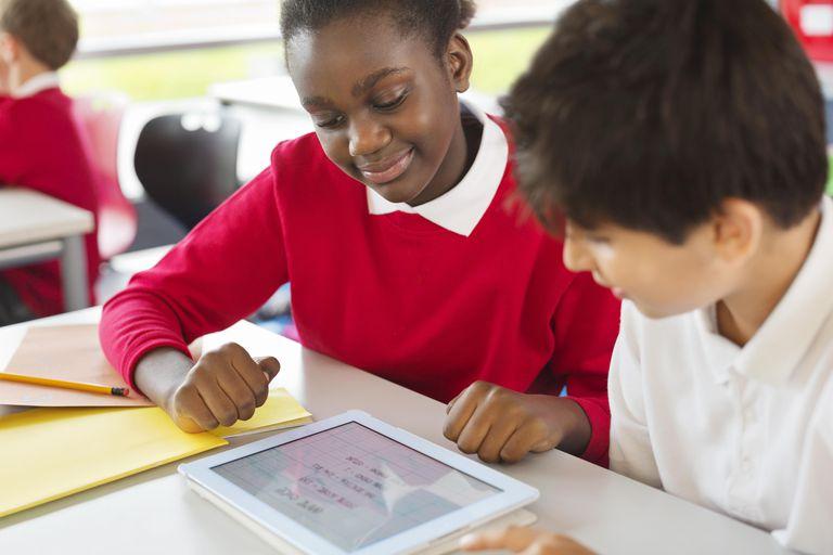 Students sharing digital tablet in classroom