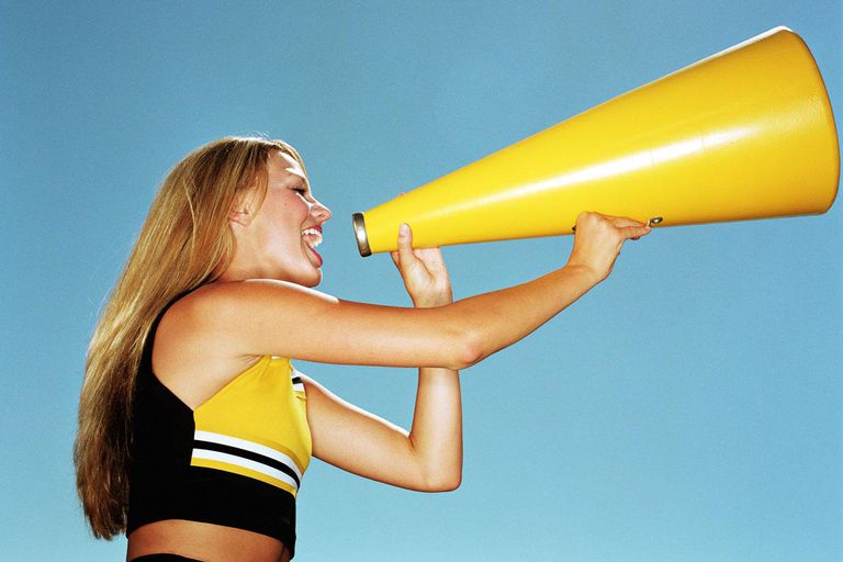 Cheerleader yelling through megaphone, low angle, side view