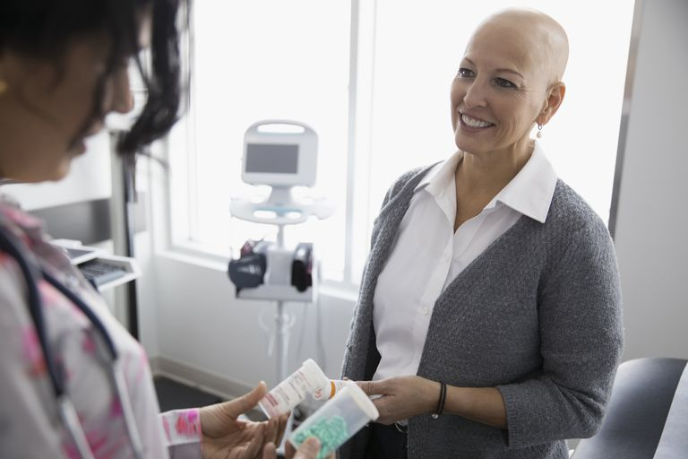 Smiling female cancer patient listening to doctor prescribing prescription medication in clinic examination room