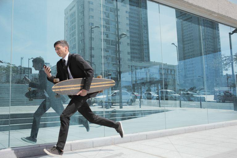 Hombre de negocios corriendo con longboard