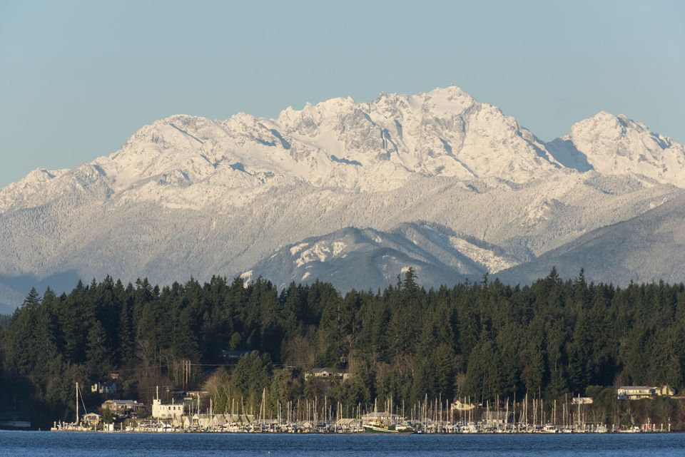 Dramatic snow covered Olympics behind Brownsville Marina in late winter, Bainbridge Island, Washington, USA