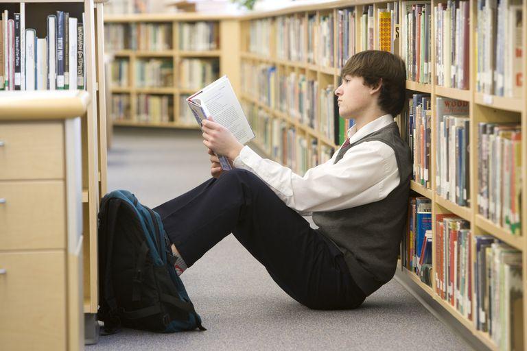 School boy (16-17) reading on floor by bookshelf in library