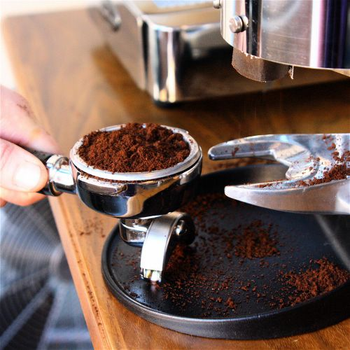 An image of a barista setting espresso grounds in a portafilter brewing basket.