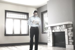 man with checklist in empty home