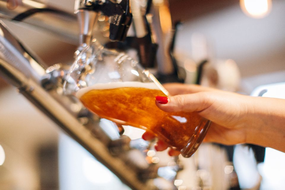 woman pouring beer in bar