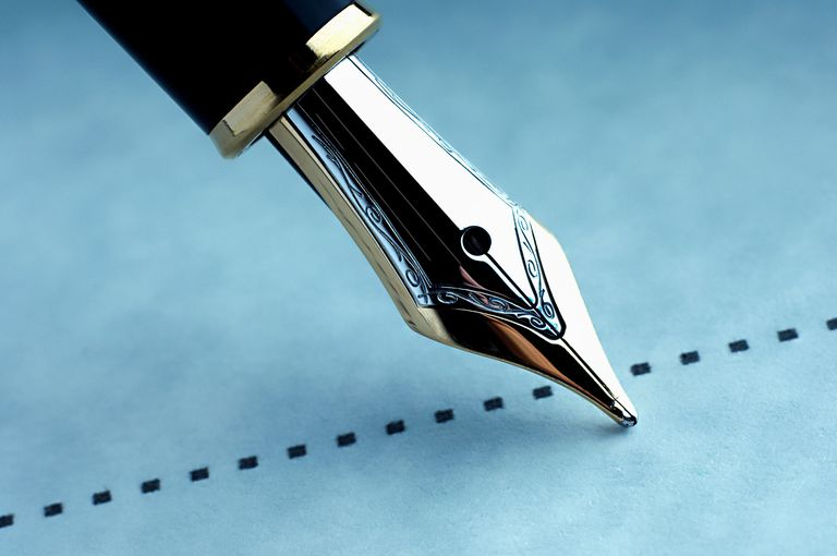 A pen signing on the dotted line on blue paper