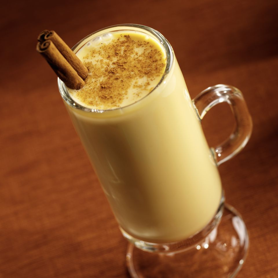 Egg nog with nutmeg and cinnamon sticks