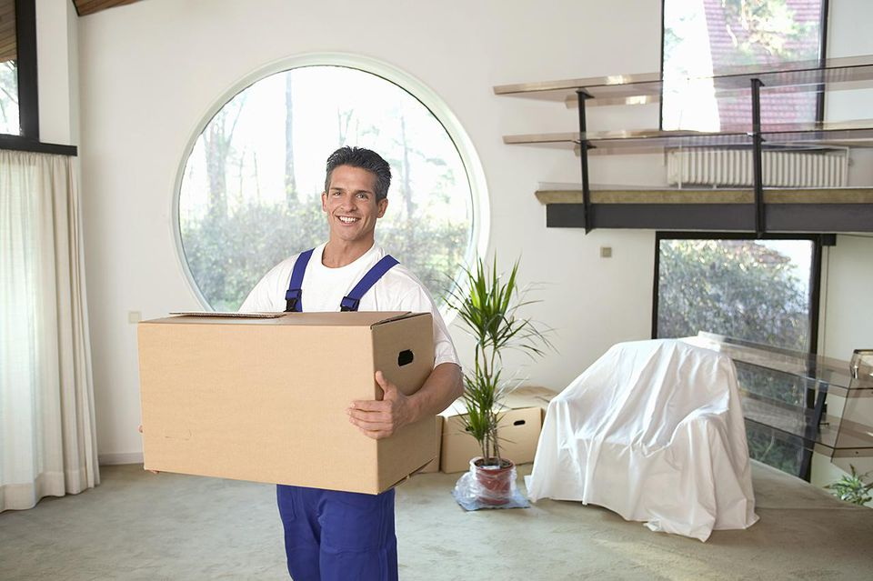 Mover holding a packed box in an empty living room